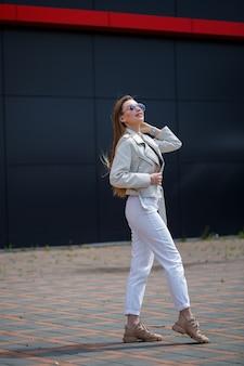 흰 블라우스와 가벼운 청바지를 입은 장발 소녀의 사진은 화창한 봄날 건물의 회색 벽 배경에 미소를 띠고 서 있습니다.
