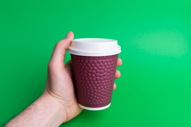 緑に紫のカップを持っている男の手の写真