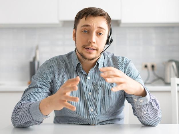 온라인 화상 통화 중 헤드셋을 가진 남자의 사진. 원거리 통신을위한 현대 기술의 개념.