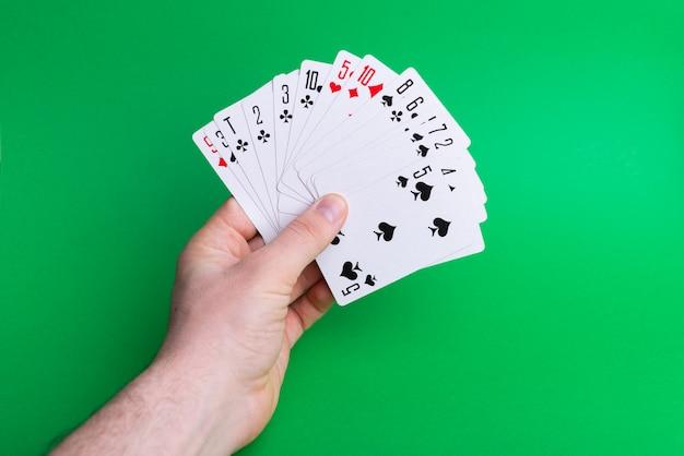 Фотография руки, держащей игральные карты на зеленом фоне