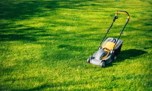 家の近くの裏庭の芝生の上に立っている現代の電気芝刈り機の写真