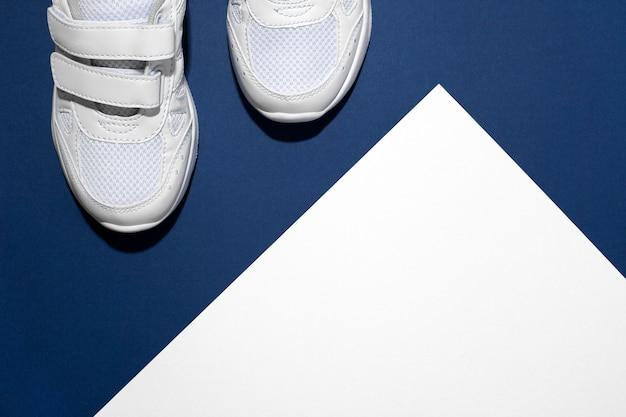 На фото пара белых детских спортивных кроссовок из кожи, обшитых тканью на липучке ...