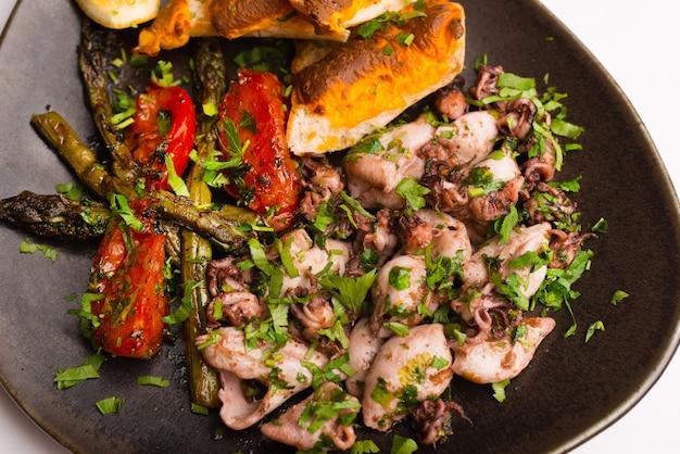 Фотография тарелки с мясом, приготовленным из моллюсков на белом фоне.
