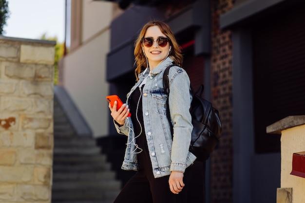긍정적 인 명랑 십대 소녀의 사진은 공원에서 시간을 보내고 휴대 전화를 사용합니다.