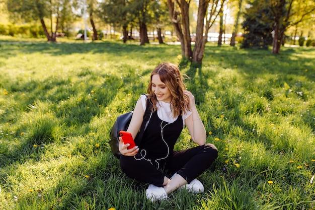 ポジティブで陽気な10代の少女の写真は、公園で携帯電話を使用して時間を過ごします。