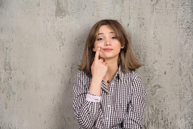 Фотография красивой девушки-модели, положившей палец на щеку