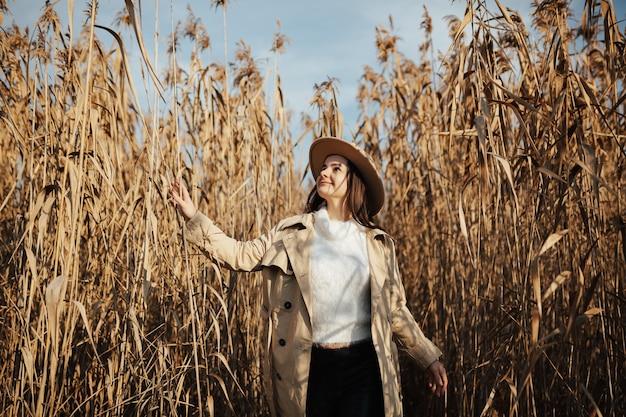 葦畑に立っている帽子をかぶったかわいい笑顔の女の子の写真。
