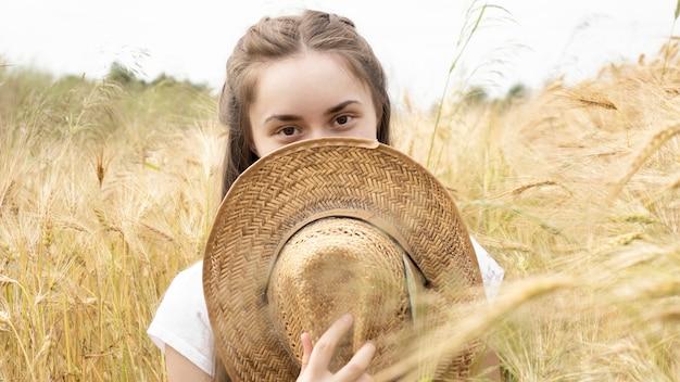 Фотография красивой молодой девушки, улыбающейся и закрывающей лицо соломенной шляпой во время прогулки