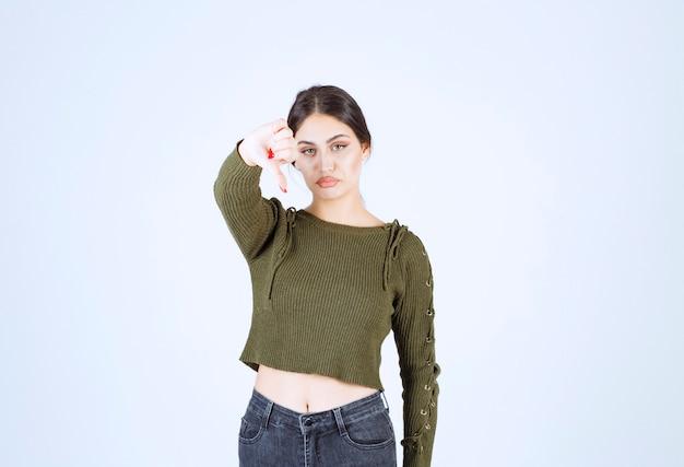 Фотография грустной молодой женщины, стоящей и показывающей большой палец вниз.