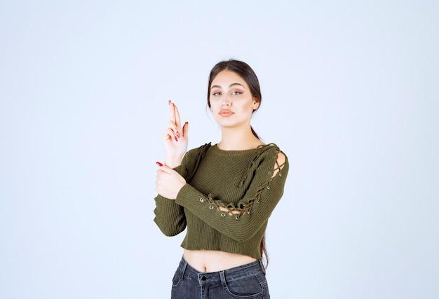 手と指でピストルをしている真面目な若い女性モデルの写真。