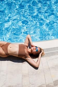 갈색 수영복에 수영장 근처에서 휴식을 취하는 비키니를 입은 금발 머리를 가진 섹시한 아름다운 여성의 사진이 놓여 있다