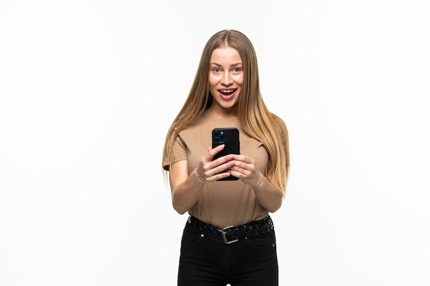 Фотография шокированной положительной эмоциональной удивленной молодой женщины, позирующей изолированной над белой поверхностью стены с помощью мобильного телефона.