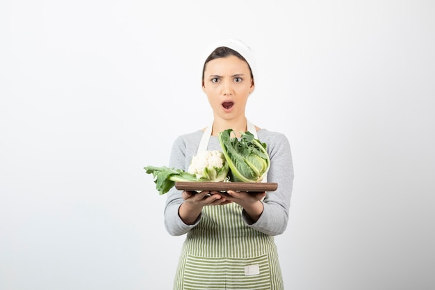 콜리플라워가 든 나무 접시를 들고 앞치마를 입은 충격을 받은 여성의 사진