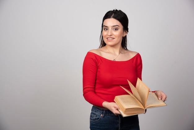 열린 책을 들고 서서 포즈를 취하는 웃는 여자의 사진.