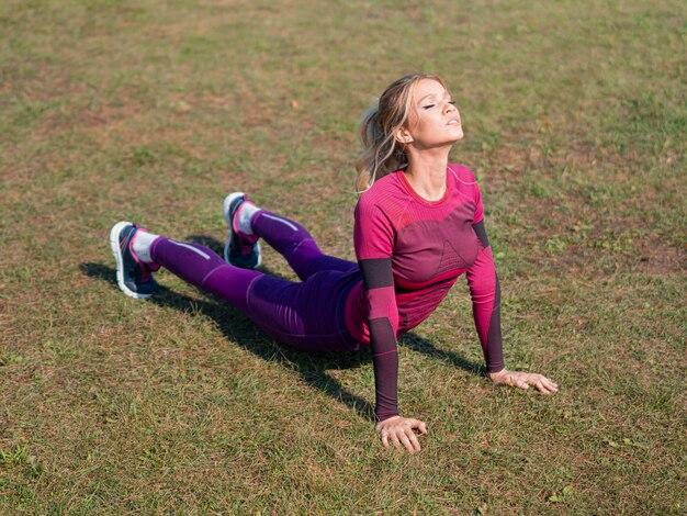 Фотография улыбающейся женщины растягивает мышцы на открытом воздухе в солнечный день. концепция здорового образа жизни.