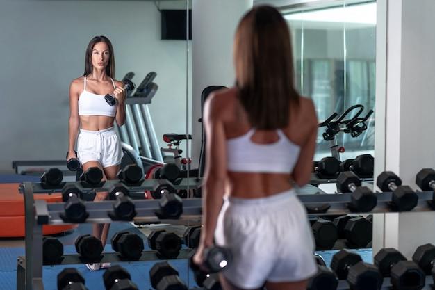 白いメッシュのトップに身を包んだスポーツ少女の写真、白いスポーツショーツはジムで鏡に映った自分の姿を手にダンベルで見ています。モデルの背面からの写真。ジム。ダンベルの場所。