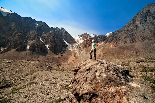배경에 있는 알타이 산맥에 있는 관광 소녀의 사진은 볼쇼이 악트루 빙하입니다