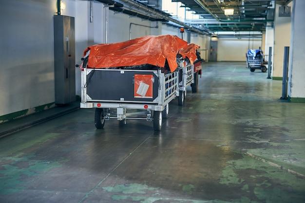 輸送の準備ができているバッグとスーツケースを満載したトロリーの写真