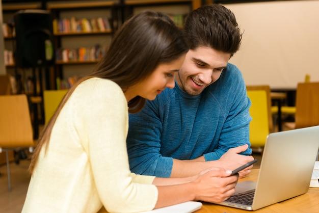 読書を勉強し、ラップトップコンピューターを使用して宿題をしている図書館で2人の若い学生の友人のカップルの写真。