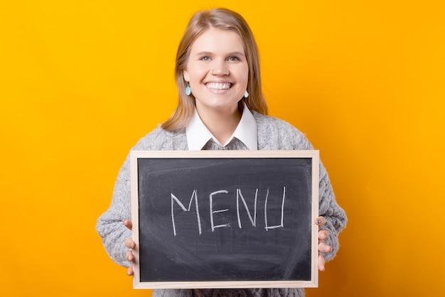 単語メニューが書かれた黒板を持っている女性の写真