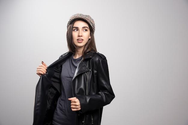 黒革のジャケットとキャップで目をそらしている女性の写真。