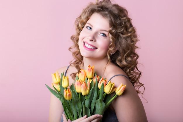 Фотография женщины со счастливой улыбкой на лице, держащей цветы в руках, сделанная на розовом фоне.