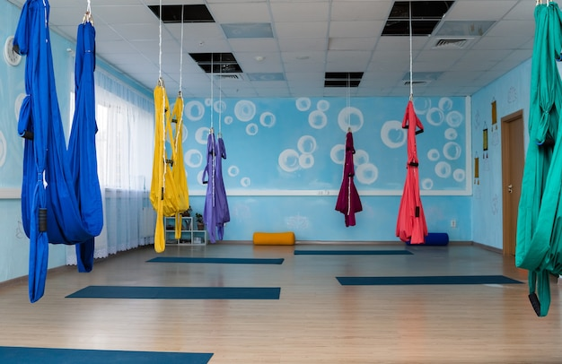 Фото зала для йоги с гамаками и ковриками