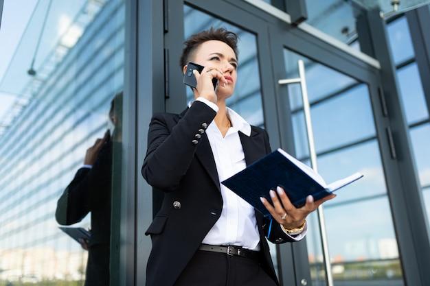 Фото молодой амбициозной бизнес-леди на современное офисное здание