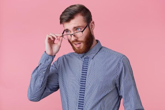 젊은 매력적인 수염 난 남자의 사진, 그의 안경을 통해 비승 인적으로보고, 동료는 직장에서 어리석은 실수를 저질렀습니다. 분홍색 배경 위에 절연.