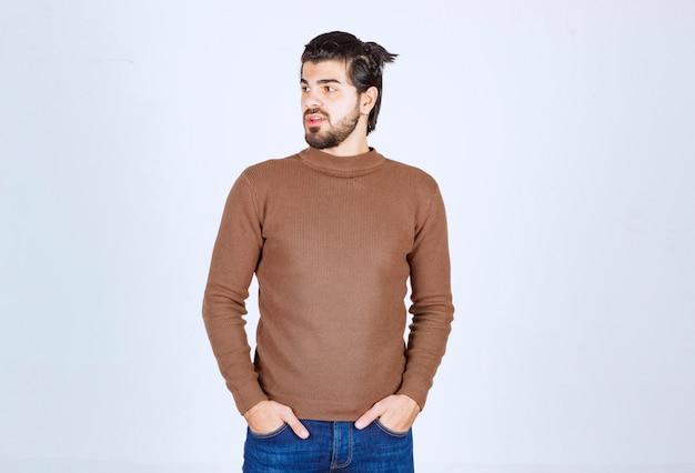 Фото молодой привлекательной модели человека стоя и глядя на белую стену. фото высокого качества