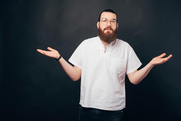 カメラを見ているわからないジェスチャーを示す若いひげを生やした男の写真