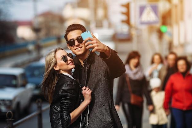 にぎやかな街の通りで自分撮りをしている若い美しいカップルの写真
