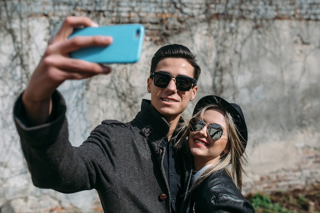灰色の壁に自分撮りをしている若い美しいカップルの写真