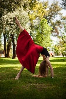 公園で若いベリーダンサーの写真若いブロンドは自然の女の子の体操選手で踊っています