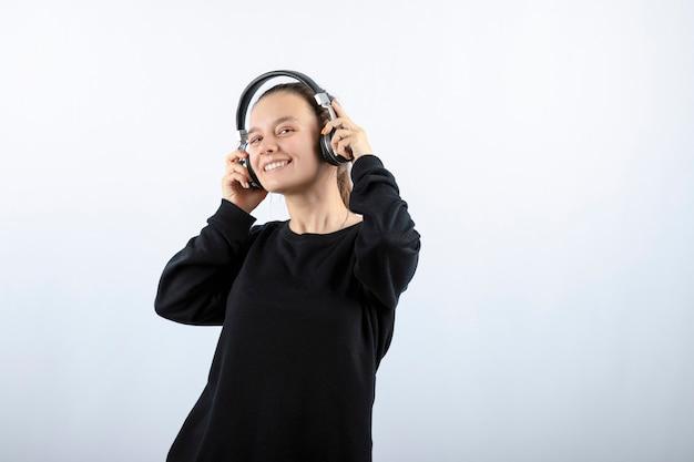 헤드폰에서 어린 소녀 모델 듣는 음악의 사진