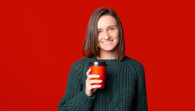 Фотография молодой женщины, держащей красную бумажную чашку кофе на вынос.