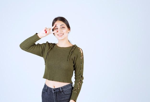 V 표시를 보여주는 젊은 사랑스러운 여자 모델의 사진