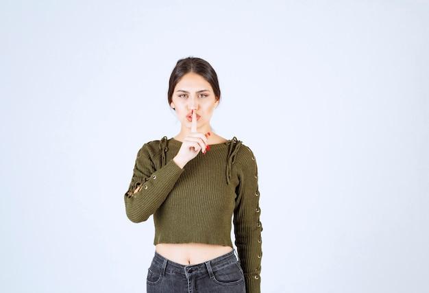 立ってサイレントサインをしている若い素敵な女性モデルの写真