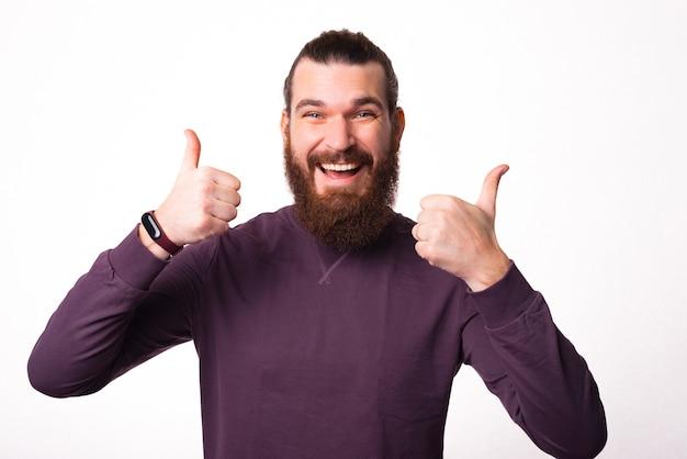 カメラに向かって微笑んで、親指を上げて両手を持ち上げている若い男の写真