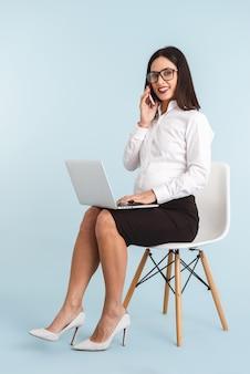휴대 전화로 얘기하는 랩톱 컴퓨터를 사용 하여 격리하는 젊은 임신 비즈니스 여자의 사진.