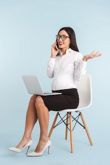 Фотография молодой беременной деловой женщины, изолированной с помощью портативного компьютера, разговаривает по мобильному телефону.