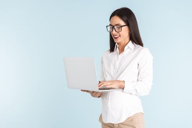 ラップトップコンピューターを使用して分離された若い妊娠中のビジネス女性の写真。