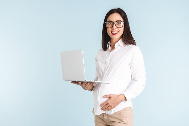 Фотография молодой беременной деловой женщины, изолированной с помощью портативного компьютера.