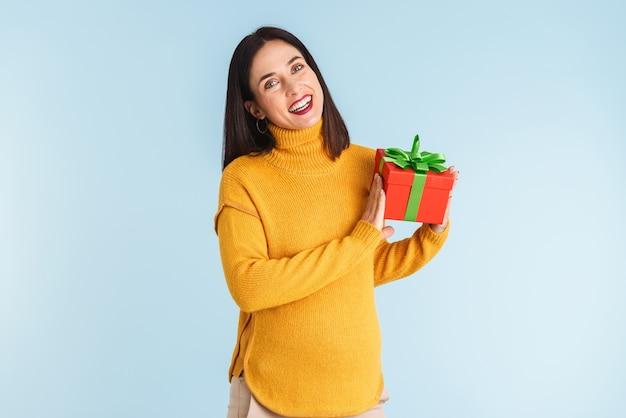 선물 상자를 들고 고립 된 젊은 임신 한 여자의 사진.
