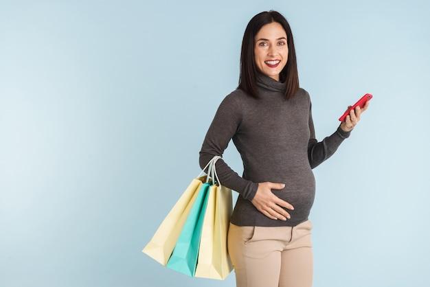 Фотография молодой беременной женщины, изолированной с помощью мобильного телефона, держащего хозяйственные сумки.
