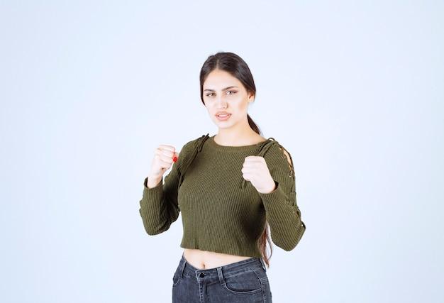白い壁越しに拳を見せる若い真面目な女性モデルの写真。