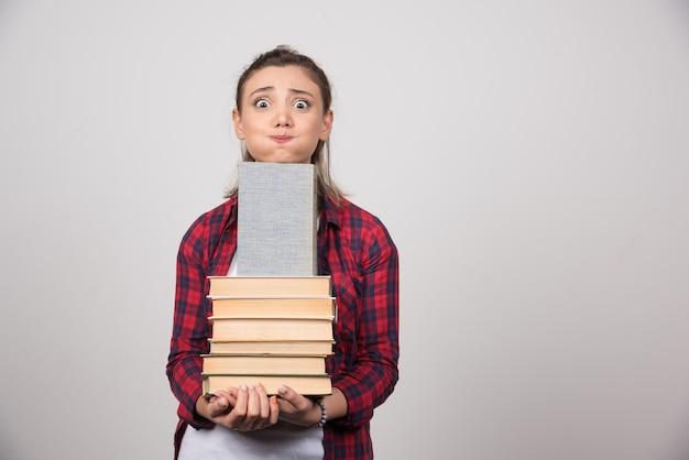 本の山を持っている若い学生の写真。