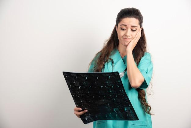 Фото молодой женщины-доктора расстроены позируя с рентгеновским снимком над белой стеной.