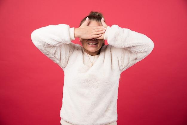 Фотография молодой женщины, закрывающей глаза руками