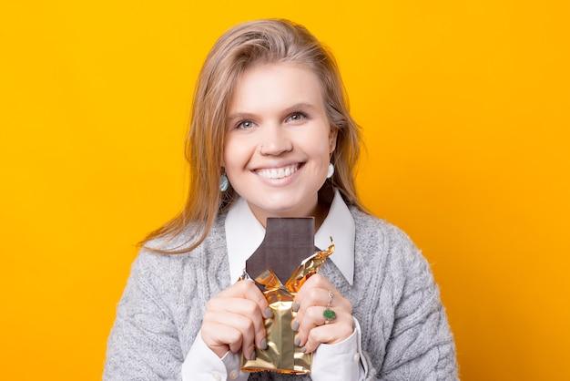 Фотография молодой женщины, едящей шоколад